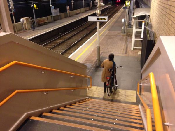 自転車を持って階段を下る女性